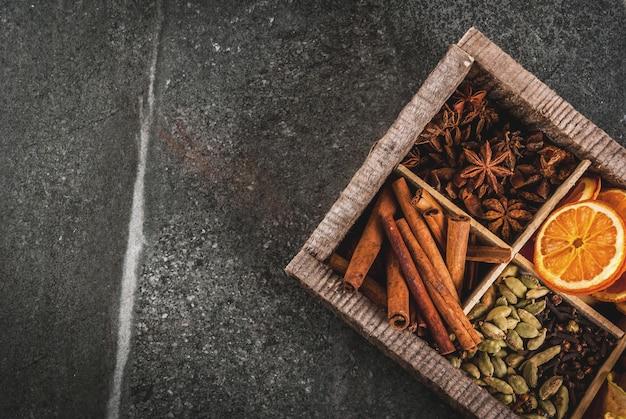 Kerstkruiden voor het bakken, cocktails, glühwein, met peperkoekkoekjes (sterren) - gedroogde appel, sinaasappel, kardemom, kruidnagel, kaneel, anijs. oude houten kist, zwarte stenen tafel. kopie ruimte bovenaanzicht