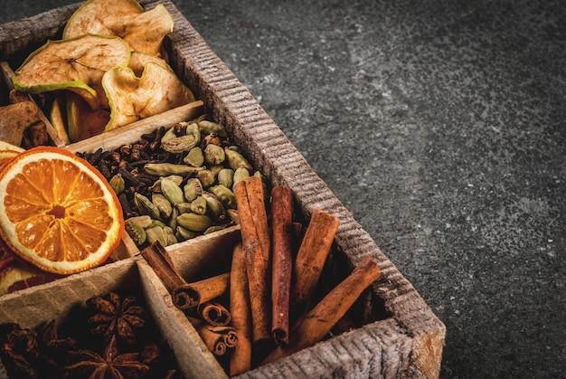 Kerstkruiden voor het bakken, cocktails, glühwein, met peperkoekkoekjes (sterren) - gedroogde appel, sinaasappel, kardemom, kruidnagel, kaneel, anijs. oude houten kist, zwarte stenen tafel. kopie ruimte