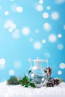 Kerstlantaarn op sneeuw met spartak en winterdecoratie op blauw. vakantie kerst concept.