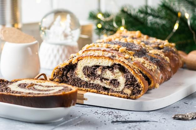 Kerstmaanzaadcake, gesneden maanzaadcake bedekt met glazuur en versierd met rozijnen en walnoten