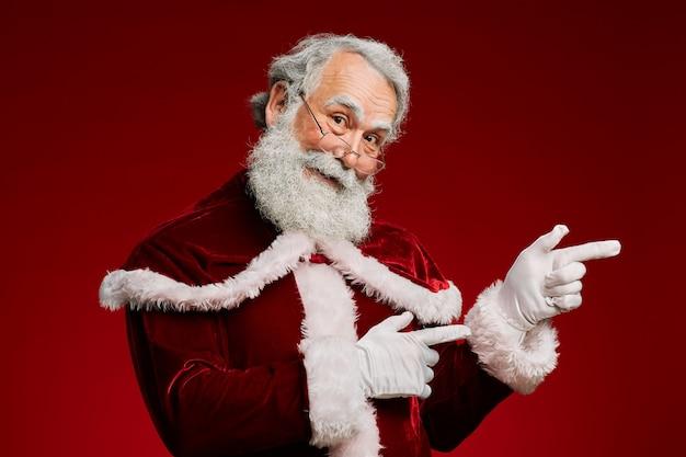 Kerstman die aan kant op rode achtergrond richten