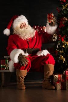 Kerstman die giften plaatsen onder kerstboom in donkere ruimte