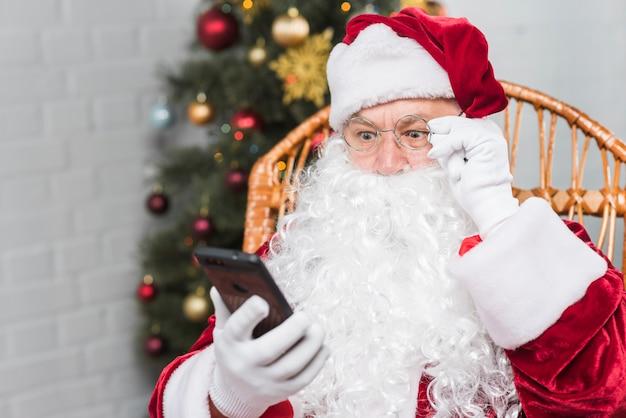 Kerstman die op schommelstoel zitten en telefoon bekijken