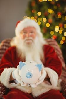 Kerstman die spaarvarken aanbiedt