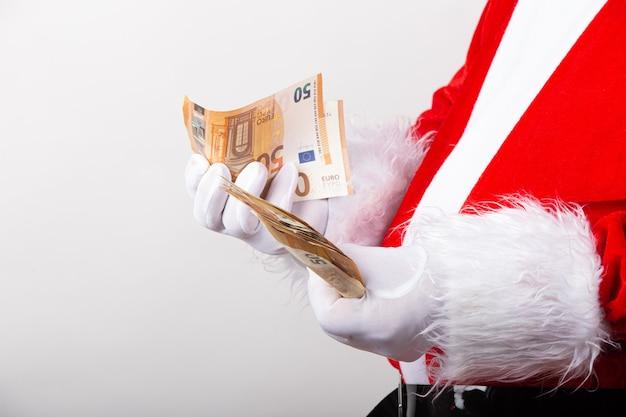 Kerstman die vijftig euro-bankbiljetten in profiel tellen voor camera die op witte achtergrond wordt geïsoleerd.