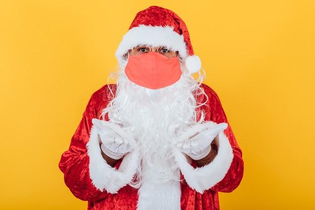 Kerstman draagt een rood gezichtsmasker met een gebaar van berusting, op geel