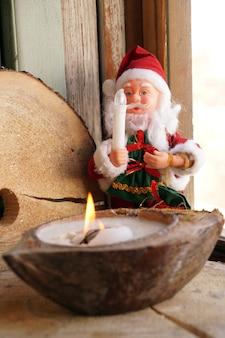 Kerstman en een kaars in een decoratieve kokosnoot
