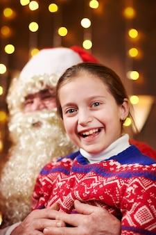 Kerstman en kind meisje poseren samen binnen in de buurt van ingericht