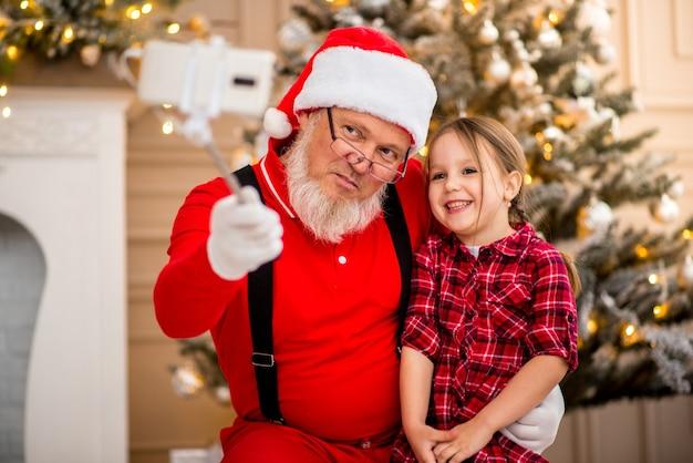 Kerstman en kind thuis tegen kerstboom. familie vakantie concept.