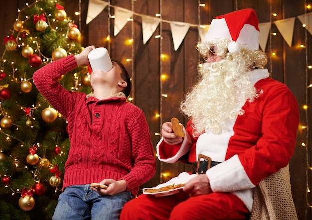 Kerstman en kindjongen die thee drinken die koekjes eet
