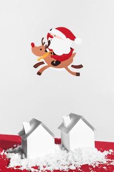 Kerstman en rendieren die boven huizen vliegen