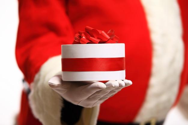 Kerstman gehandschoende handen met geschenkdoos Premium Foto