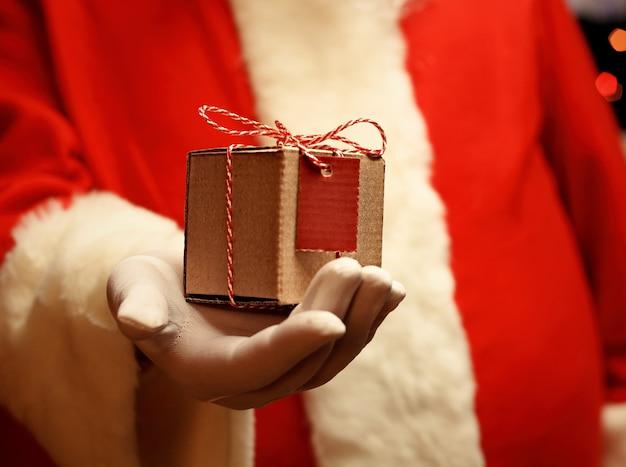 Kerstman gehandschoende handen met geschenkdoos
