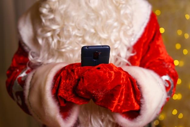 Kerstman hand in wanten houdt smartphone in zijn handen lange witte baard rood pak modern russisch