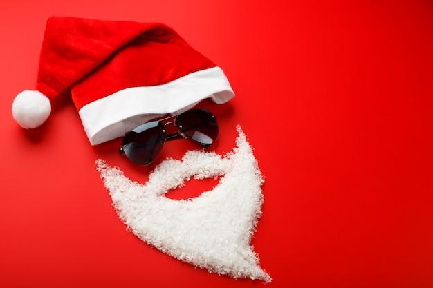 Kerstman hoed en baard gemaakt van sneeuw met zwarte bril