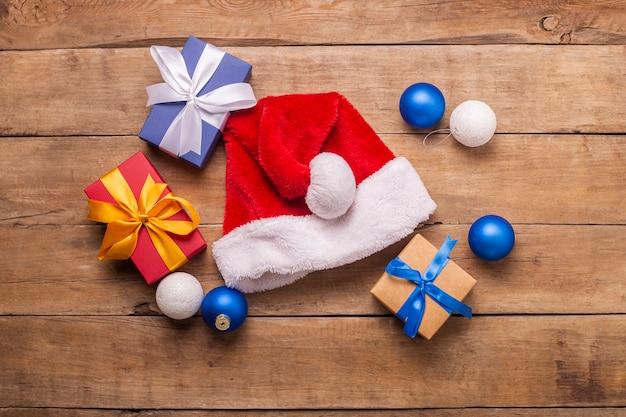 Kerstman hoed en geschenken op een houten achtergrond. concept voor kerstmis, nieuwjaar. bovenaanzicht, plat gelegd.