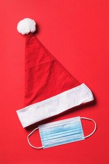 Kerstman hoed en medisch masker op een rode achtergrond bovenaanzicht