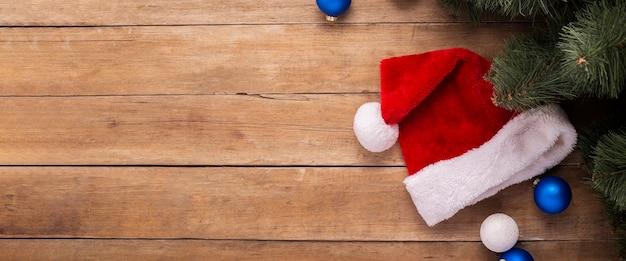 Kerstman hoed, geschenken en takken van een kerstboom op een houten achtergrond. bovenaanzicht, plat gelegd. banier.