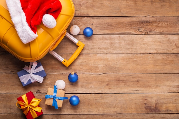 Kerstman hoed, koffer, geschenken op een houten achtergrond. bovenaanzicht, plat gelegd.