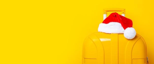 Kerstman hoed ligt bovenop een gele koffer op een gele achtergrond. banier.