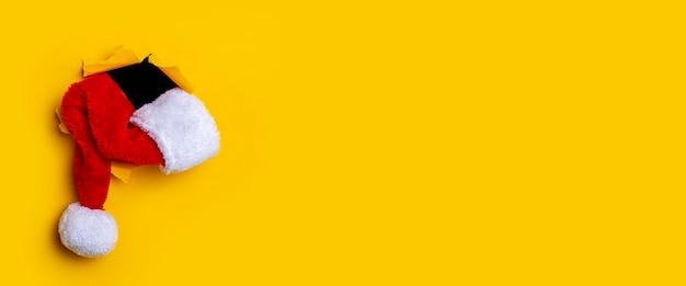 Kerstman hoed ligt in een gat in de gescheurde gele achtergrond. banier.