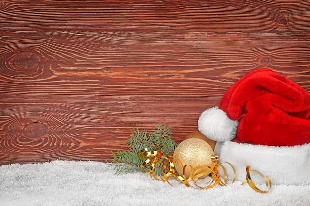 Kerstman hoed met kerstversiering op houten oppervlak