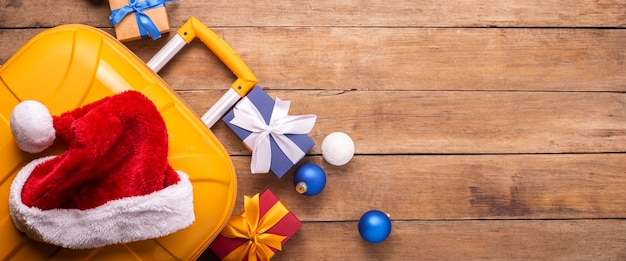 Kerstman hoed op een gele koffer op een houten achtergrond. bovenaanzicht, plat gelegd. banier.