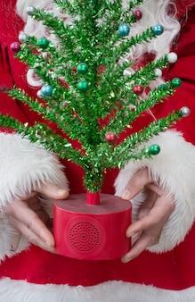 Kerstman houdt kerstboom kerstboom in santa's handen vakantie concept