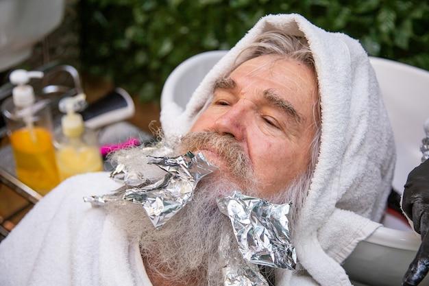 Kerstman in de schoonheidssalon scheren en kleuren van zijn haar. bebaarde en harige senior in de schoonheidssalon