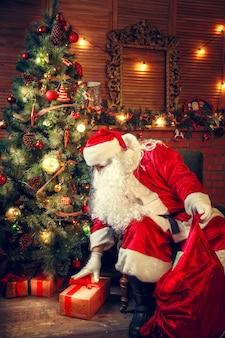 Kerstman in de woonkamer. de kerstman stopt cadeaus in een zak