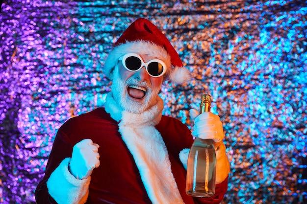 Kerstman in rood kostuum en in zonnebril fles champagne houden en nieuwjaar vieren