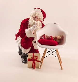 Kerstman in rood kostuum met een baby die op wit wordt geïsoleerd