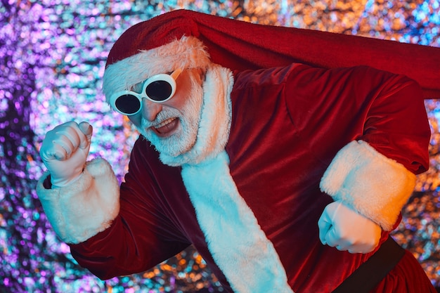 Kerstman in zonnebril en in kostuum rennen voor vakantie