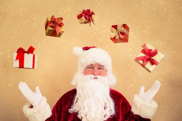 Kerstman jongleren met kerstcadeaudozen. kerst vakantie concept