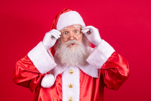 Kerstman kijken naar de camera. kerst komt eraan. vrolijk kerstfeest. de kerstman kijkt toe. hij houdt zijn bril vast.
