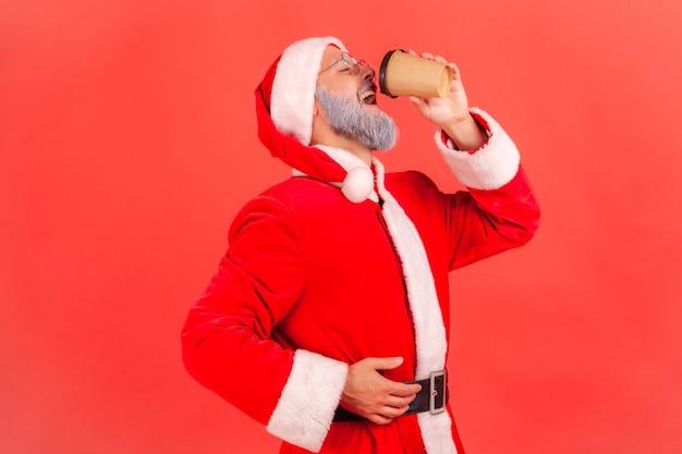 Kerstman koffie drinken uit papieren beker, gebrek aan energie, genieten van warme drank.