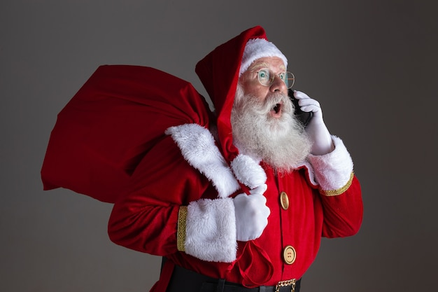 Kerstman met behulp van een smartphone. verrast.