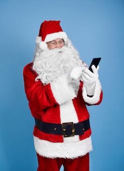 Kerstman met behulp van mobiele telefoon op studio-opname