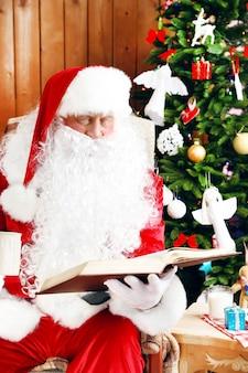 Kerstman met boek zittend in comfortabele schommelstoel in de buurt van kerstmis thuis