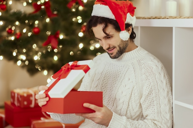 Kerstman met cadeau in de geschenkdoos bij de kerstboom thuis