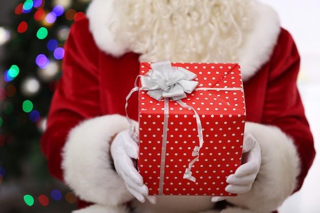 Kerstman met cadeau op het oppervlak van de kerstboom