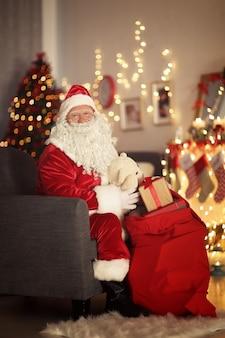 Kerstman met cadeauzakje in kamer versierd voor kerstmis