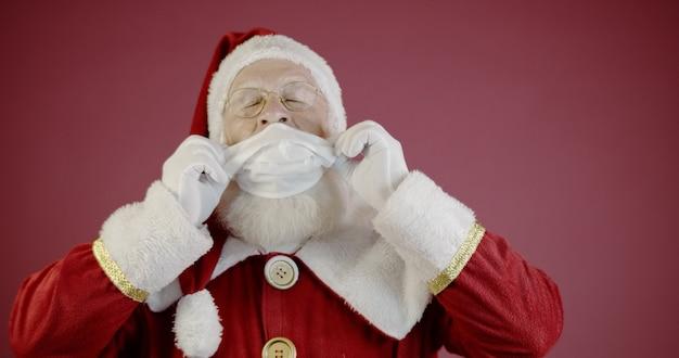 Kerstman met covid-19, met een beschermend gezichtsmasker. kerst 2020. pandemie