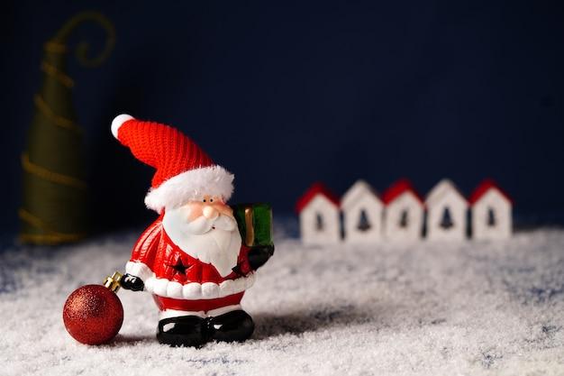 Kerstman met een cadeau op de achtergrond van kleine huisjes en een kerstboom