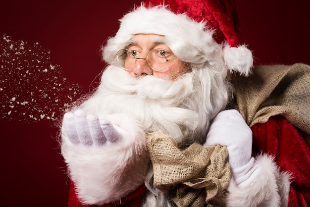 Kerstman met een geschenkdoos op rode achtergrond