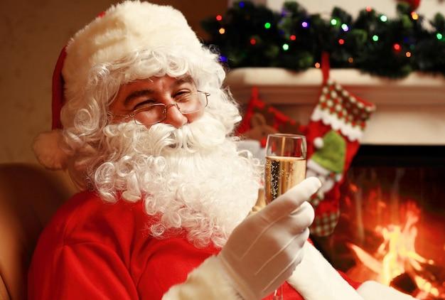 Kerstman met een glas mousserende wijn champagne in de buurt van een kerstboom