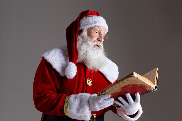 Kerstman met een oud rood omslagboek. namen opschrijven cadeaus voor kerstmis. kerst komt eraan