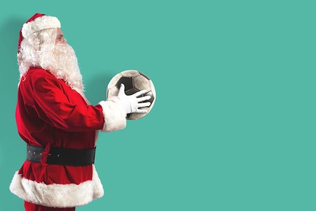 Kerstman met een voetbal in zijn handen geïsoleerd op een mintkleurige achtergrond