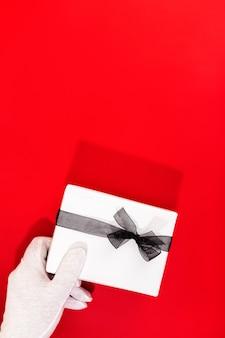 Kerstman met gehandschoende handen met een kerstcadeau.