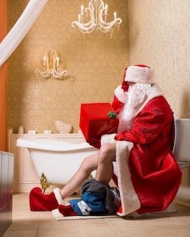 Kerstman met geschenkdoos zittend op het toilet